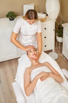スパサロンで若いきれいな女性のクライアントのために顔にマッサージをしている若い女性マッサージ師のクローズアップショット。
