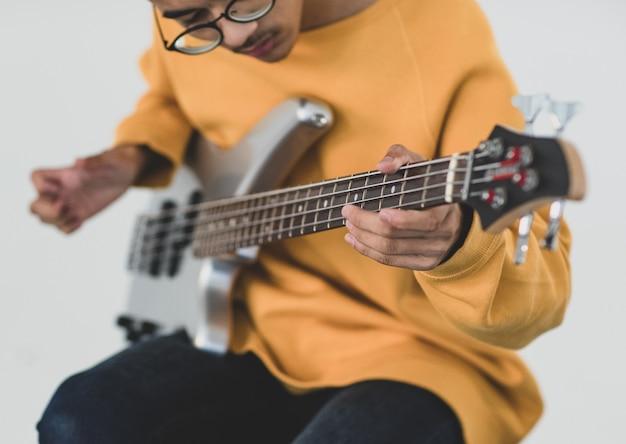ベースギターを弾く若い男性ミュージシャンの手のクローズアップショット。ベーシストの手と白い背景で隔離されたベースギターに選択的な焦点。青年期のライフスタイルと音楽の概念