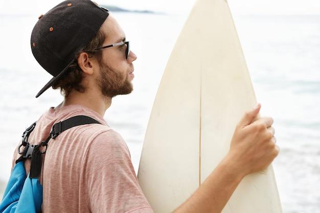 Крупным планом снимок молодого серфера со стильной бородой в рюкзаке и бейсболке, держащего белую доску для серфинга, стоящего на пляже и смотрящего на океан