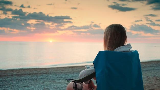 魔法瓶から飲んで、ビーチのキャンプチェアに座っている若い女性のクローズアップショット。