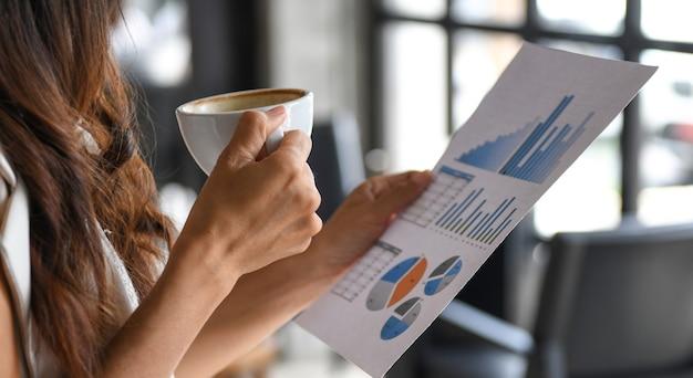 Крупным планом молодых женщин держать чашку кофе и проверить график данных.