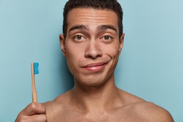Крупным планом - молодой человек со здоровой кожей, сильным телом, держит зубную щетку, собирается на утренние гигиенические процедуры, стоит у синей стены. концепция гигиены, ухода за зубами и красоты