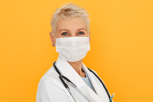 Close up shot og middle aged female epidemiologist investigating patterns, causes and injury of contagious disease, wearing medical mask
