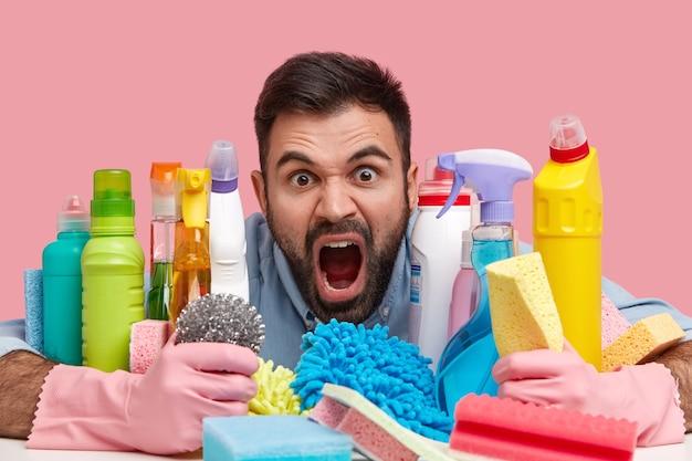 Il primo colpo di uomo con la barba lunga indignato apre ampiamente la bocca, ha la barba scura, esclama negativamente, essendo molto emotivo, stufo della stanza delle pulizie