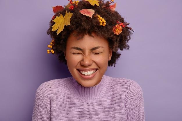 Immagine ravvicinata di donna riccia felicissima si diverte al coperto, essendo intrattenuta, chiude gli occhi con soddisfazione e gioia, mostra denti bianchi, fogliame autunnale in testa