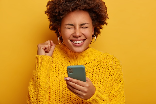Close up shot of overjoyed curly woman keeps fist clenched, happy to get money reward, gets notification on cellphone, wears yellow knitted sweater