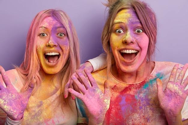 Immagine ravvicinata di due donne emotive felicissime che aprono la bocca, esclamano con gioia, hanno colorato la festa, si sono spalmate a vicenda con polvere colorata, stupite nel vedere qualcosa di incredibile sul festival indiano