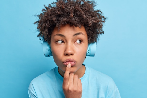 Close up shot of pensive afro american female student with audio lessons wears stereo headphones on ears has thoughtful expression while listening educative content.