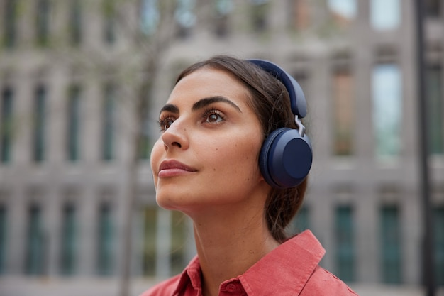 Close up shot of pensive brunette female model listens music from playlist wears wireless headphones walks outside during daytime thinks about something discovers new city and places of interest