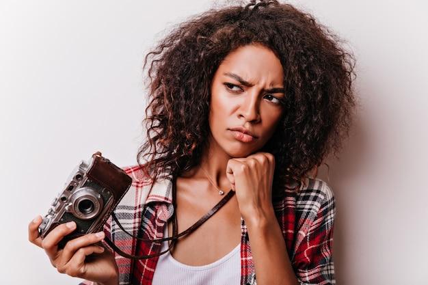 Close-up shot di pensieroso shotgrapher femminile. accattivante ragazza africana con i capelli ondulati corti che tiene la macchina fotografica.
