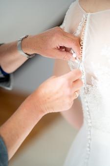 Immagine ravvicinata di una persona che aiuta a zip il bellissimo abito da sposa
