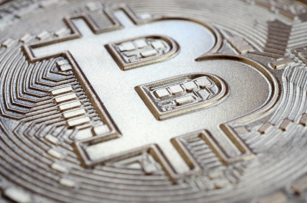 Close up shot of a physical bitcoin with a shiny relief surface made of chocolate