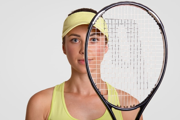 Close up shot of pleasant looking healthy woman holds tennis racket, being runner up, looks through net, wears court cap