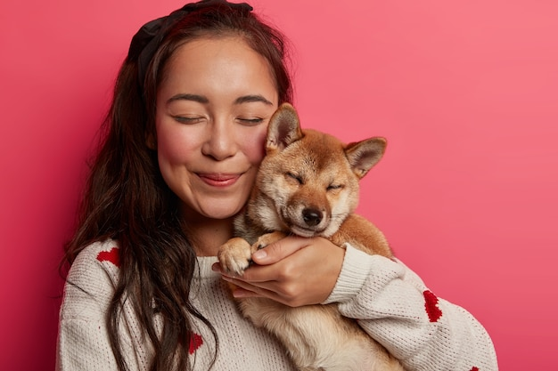 Close up shot of pleased asian woman carries pedigree dog closely near face, closes eyes from pleasure, embraces animal with love