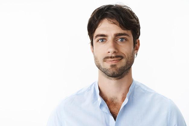 Primo piano del ragazzo maturo attraente soddisfatto con la barba e gli occhi azzurri in camicia con colletto sbottonato sorridente soddisfatto davanti tornando a casa, accolto da un cane amorevole sul muro grigio