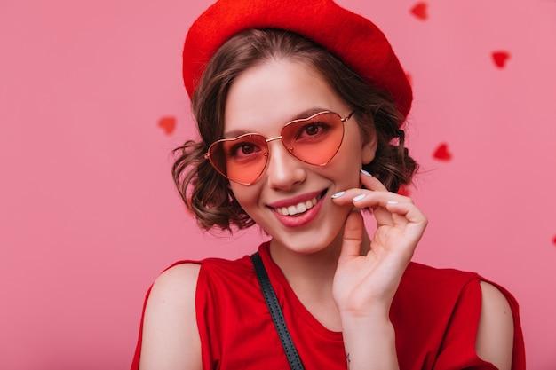 Colpo del primo piano della donna caucasica soddisfatta in bicchieri di cuore in posa con un sorriso allegro. modello femminile francese attraente che esprime felicità.