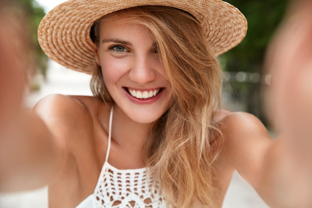 Close up shot of pleased pretty young woman makes selfie, has happy expression, wears straw hat and summer white dress, glad to pose at camera and photographing herself, expresses positiveness
