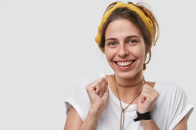 Immagine ravvicinata di donna sorridente soddisfatta con espressione felice, stringe i pugni, guarda felice