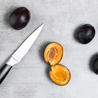 Close-up shot of plums and knife on wooden table