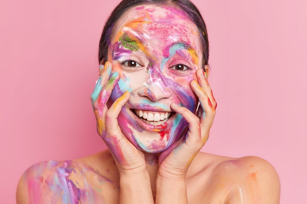 Close up shot of positive asian woman smeared with colorful gouache paints keeps hands on cheeks smiles happily