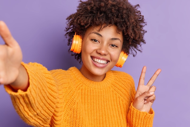 Close up shot of positive dark skinned ethnic woman makes victroy gesture smiles broadly and takes selfie listens audio track in wireless headphones