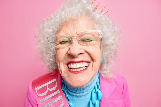 Close up shot of positive wrinkled old woman smiles toothily, wears transparent glasses princess crown on head stylish outfit applies bright makeup expresses joy