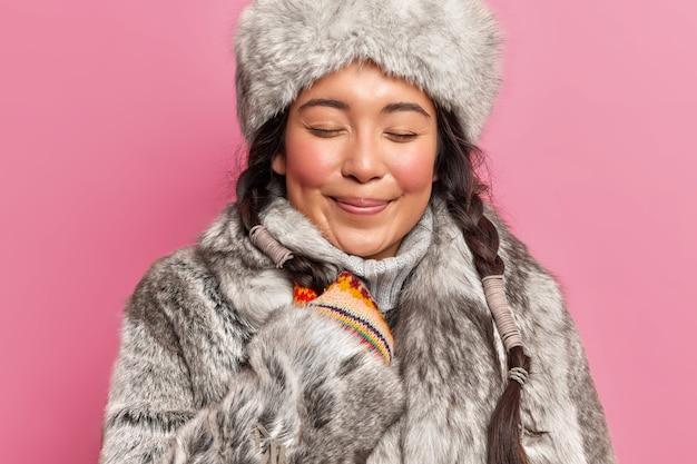 Immagine ravvicinata di bella donna orientale ha guance rosse due trecce si leva in piedi con gli occhi chiusi indossa pelliccia grigia e cappello pone contro il muro rosa