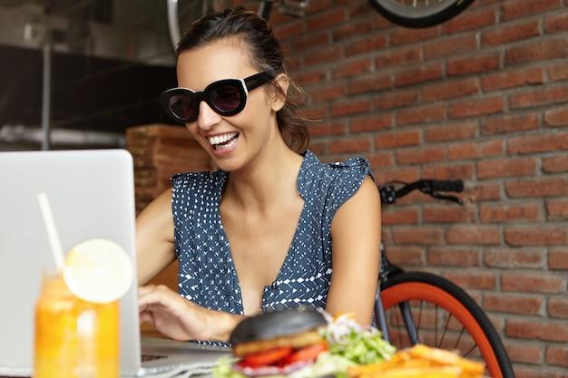 Chiuda sul colpo della donna graziosa che compera online facendo uso del computer portatile mentre mangiando il caffè, sorridendo allegramente