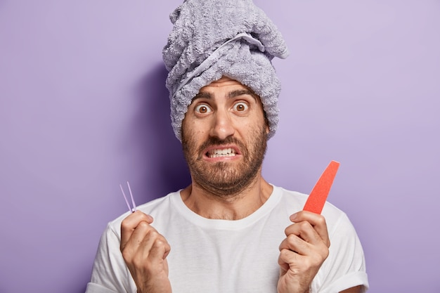 Close up shot of puzzled unshaven young guy uses fine for polishing nails, holds tweezers for plucking eyebrows