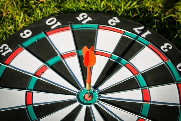Close up shot red dart arrow hitting in the target center of dartboard,business goal or target success concept.