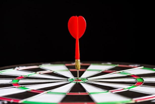 Закройте выстрел красные стрелки стрелки в целевом центре на черном фоне