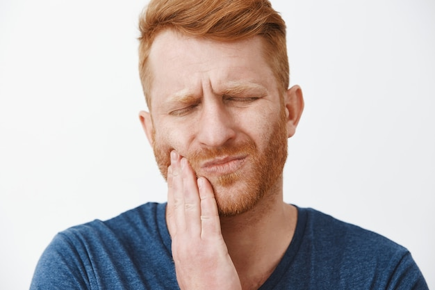 Close-up shot of redhead man with beard feeling pain in teeth, frowning and making suffering expression with closed eyes, touching cheek, having need to call dentist for curing decay or rotten tooth