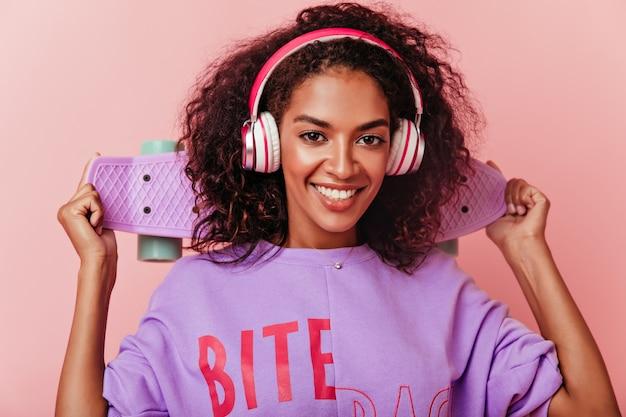 Inquadratura ravvicinata di raffinata donna nera in grandi cuffie alla moda. incredibile ragazza bruna sorridente che tiene skateboard e musica d'ascolto.