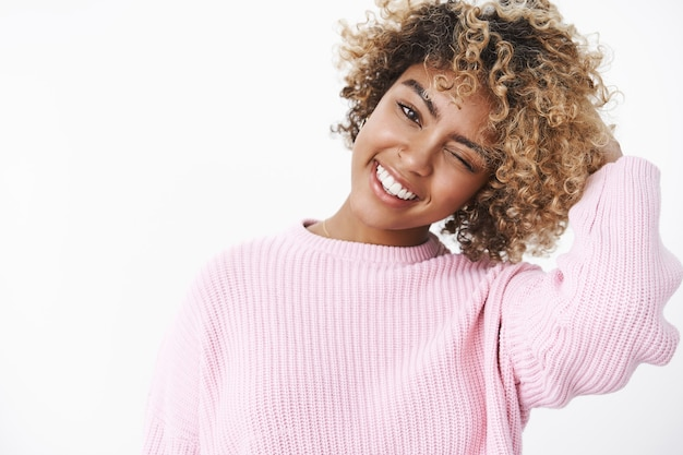 Inquadratura ravvicinata di rilassata e spensierata felice carina e tenera femmina afro-americana con taglio di capelli riccio inclinando la testa con gioia sorridente ampiamente strizzando l'occhio alla telecamera carismatico e sfacciato sul muro bianco