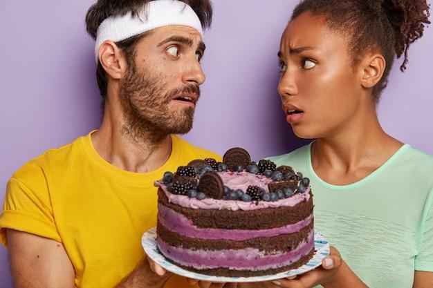 Immagine ravvicinata di triste diverse donne e uomini trattati con una deliziosa torta dopo l'allenamento sportivo, provare la tentazione, pronto da mangiare dessert