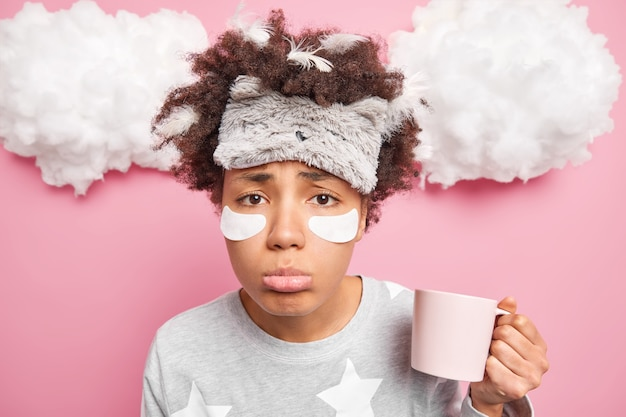 Close up shot of sad sleepy woman has feathers in messy curly hair dressed in nightwear drinks coffee from cup in morning enjoys refreshing beverage applies beauty patches under eyes stands indoor