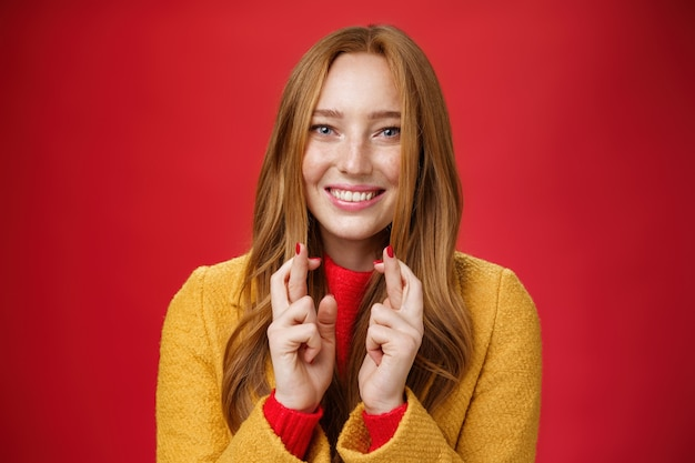 Close-up shot of satisfied happy young 20s woman in yellow coat showing thumbs up gesture in like and approval giving positive feedback enjoying nice event standing over red background, smiling cute.