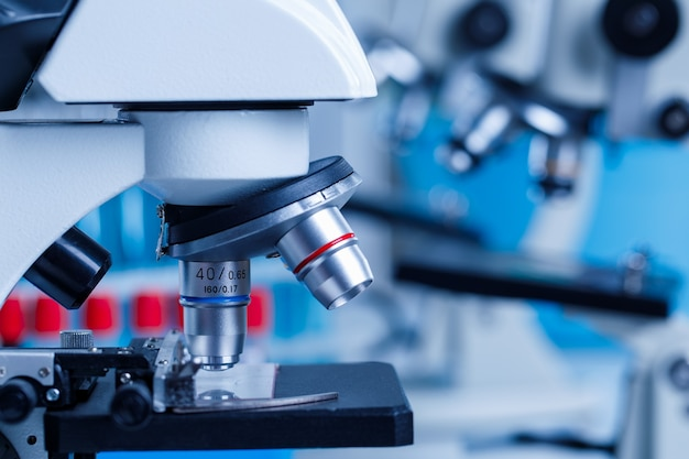 Close up shot of scientific microscope magnifying lens zooming monitoring on glass plate sample in front of blurred red and blue test tubes background in hospital laboratory.