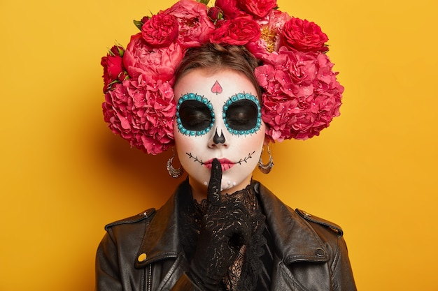 Close up shot of secret woman has sugar skull makeup makes silence gesture keeps finger over lips, stands with closed eyes dark painted circles around being charming and dangerous.