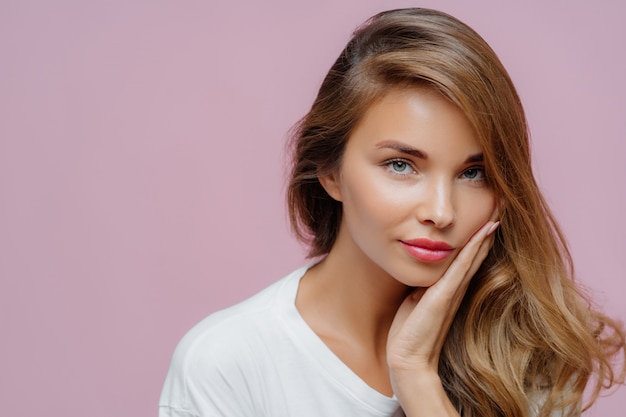 Close up shot of self confident beautiful caucasian woman has long hair combed on one side