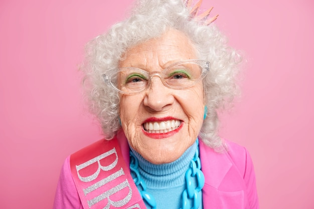 Close up shot of senior grey haired european woman smiles broadly applies bright makeup shows her perfect whit teeth celebrates birthday