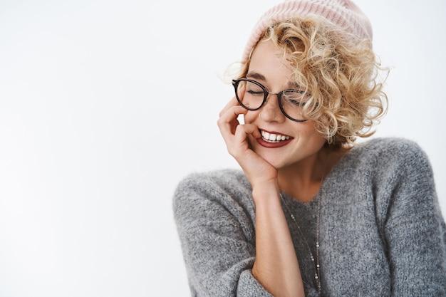 Primo piano di una donna sensuale e tenera hipster civettuola in berretto invernale e maglione chiudere gli occhi inclinando la testa e sorridendo civettuola toccando la guancia tenera e gentile, ricordando bei ricordi caldi