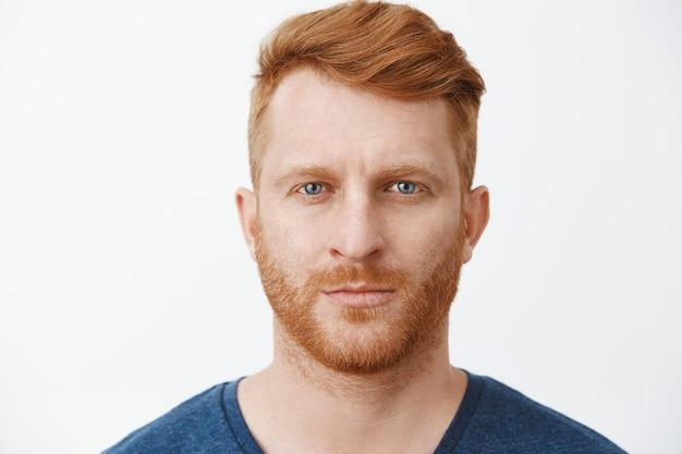 Inquadratura ravvicinata di un bell'uomo europeo adulto dall'aspetto serio con i capelli rossi e la barba che fissa con espressione concentrata e determinata, in piedi in posa rigorosa sul muro grigio