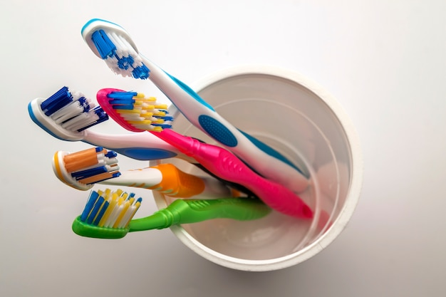 Close up shot of set of multicolored toothbrushes in glass on clean toilet on white background,  dental.