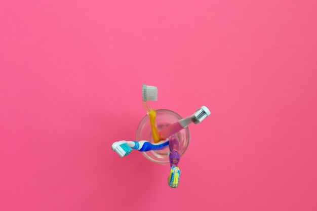 Close up shot of set of multicolored toothbrushes in a glass on pink background