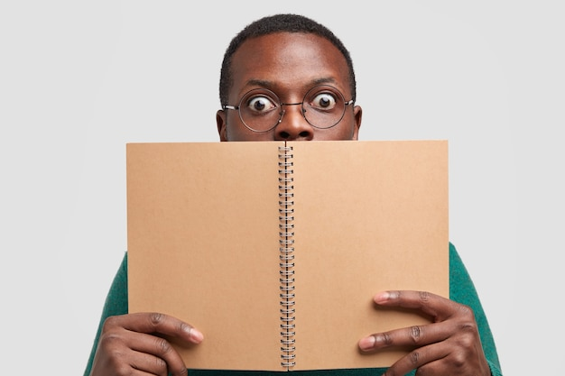 Close up shot of shocked black man covers face with spiral notepad, feels astonished, models over white studio background, reads notes written in notebook