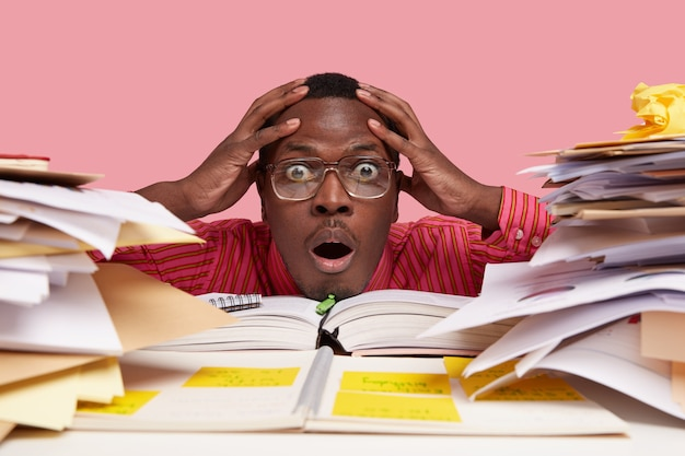 Close up shot of shocked stupefied black african american man keeps both hands on head, looks through pile of books and papers, has difficult task