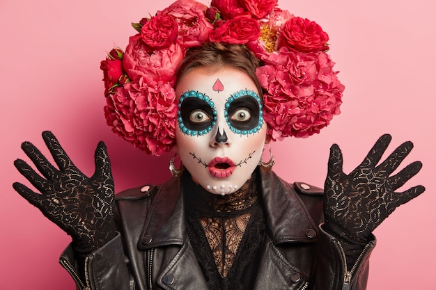 Close up shot of shocked woman wears frightening makeup, keeps palms raised, celebrates halloween or mexican day of death, isolated over pink background