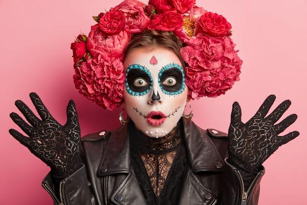 Immagine ravvicinata di donna scioccata indossa trucco spaventoso, tiene i palmi sollevati, celebra halloween o il giorno della morte messicana, isolato su sfondo rosa