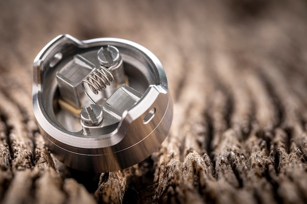 Close up shot of single space coil in high end rebuildable dripping atomizer for flavour chaser on rustic natural wood texture background, vaping device